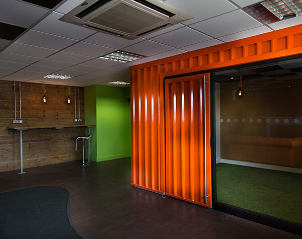 Creative thinking incorporates container, artificial turf and scaffold into employee break-out room